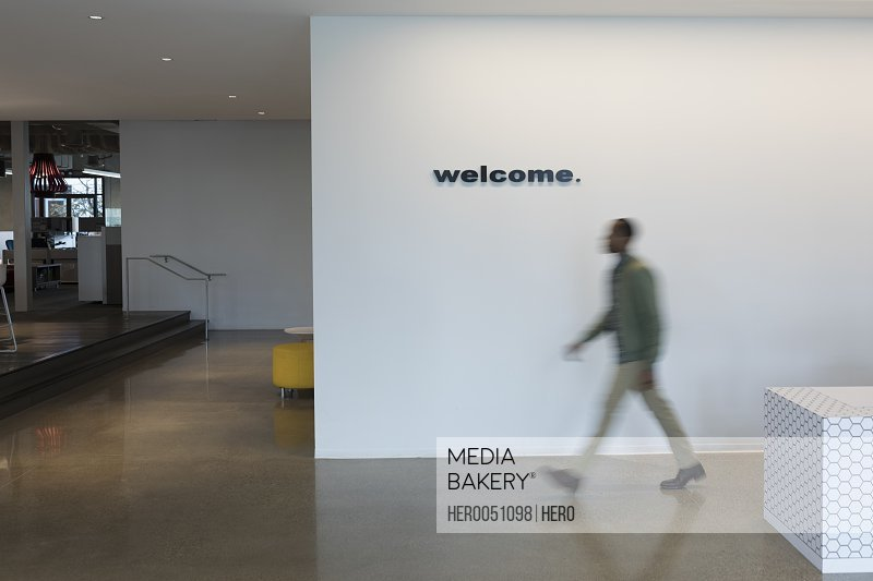 Businessman walking past welcome sign in office lobby