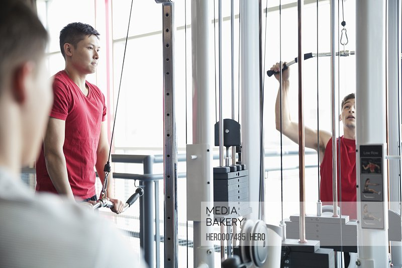 Men using weight machines in fitness center