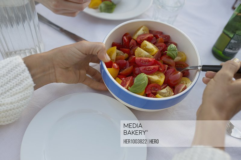 Personal perspective woman serving fresh, healthy tomato salad at table