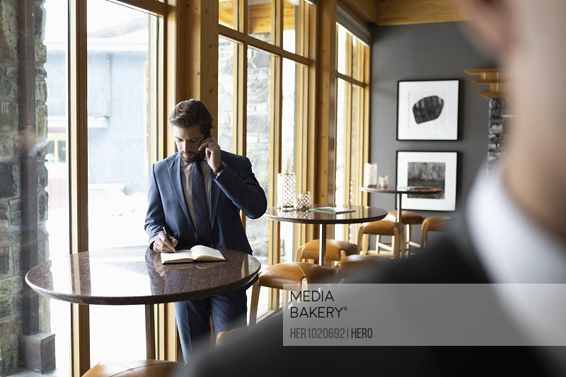 Businessman talking on smart phone and writing in notebook in bar