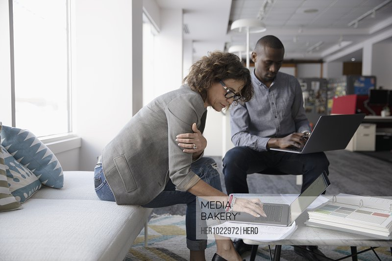 Interior designers using laptops in office