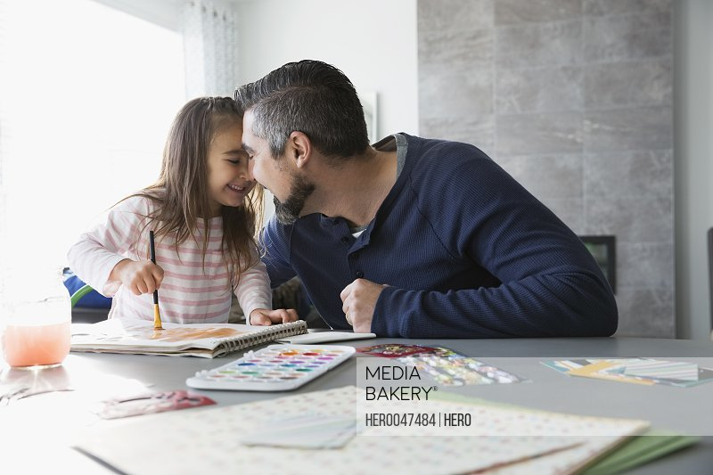 Affectionate father and daughter painting at dining room table
