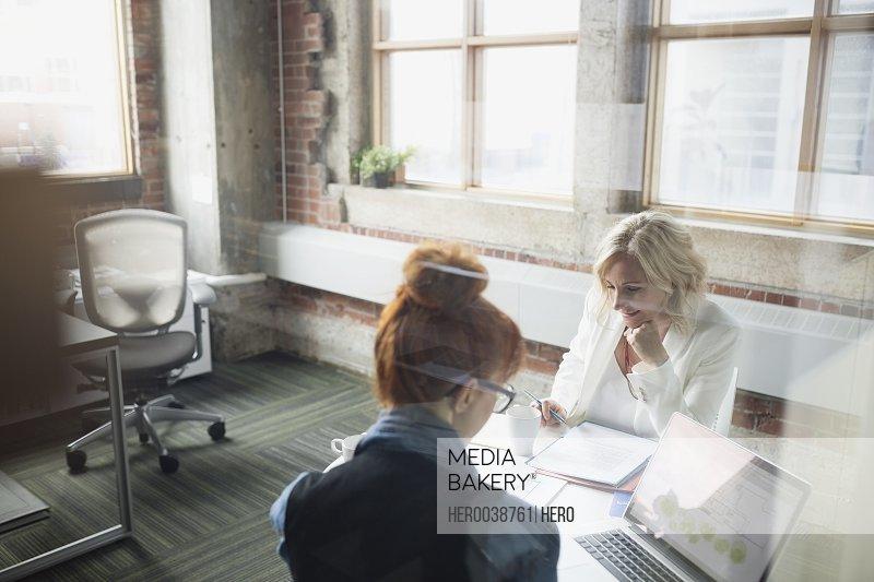 Businesswomen reviewing paperwork in meeting