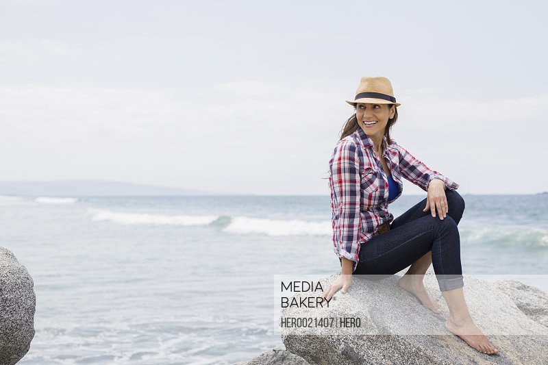 Smiling barefoot woman in hat sitting rocks ocean