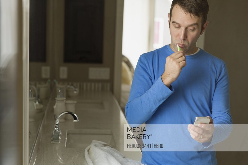 Man brushing his teeth and checking cell phone