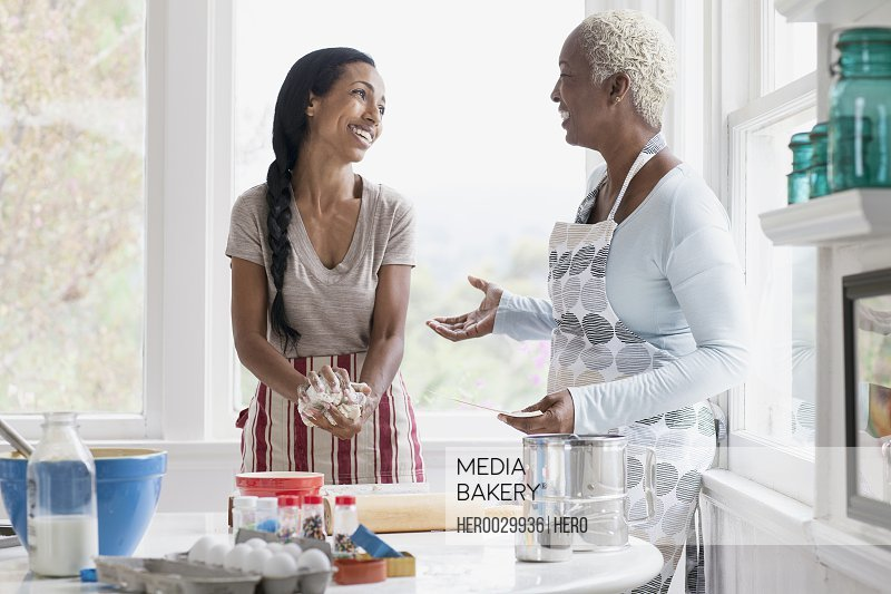 mother and adult daughter talking while preparing dough