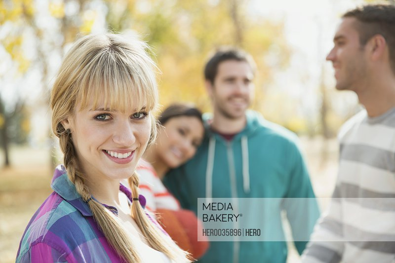 Portrait of young woman with friends in park