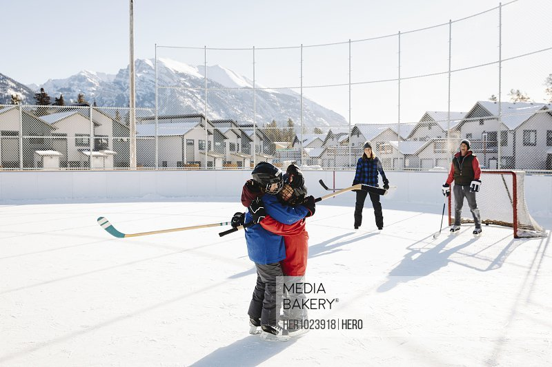Family playing outdoor ice hockey, siblings hugging