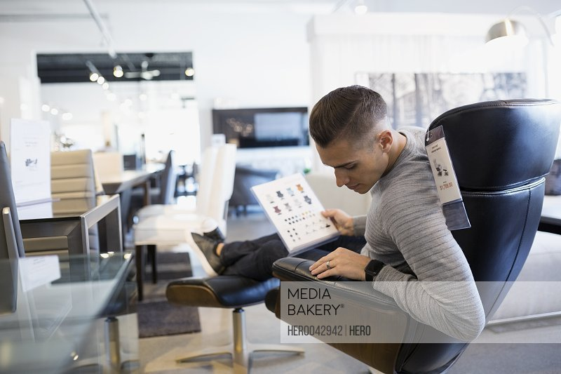 Man shopping for leather chair in home furnishings store