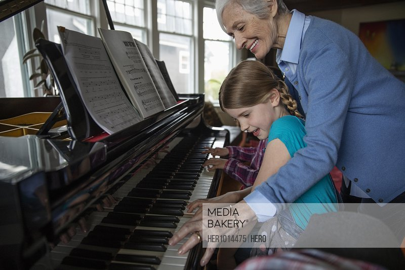 Grandmother teaching granddaughter how to play piano
