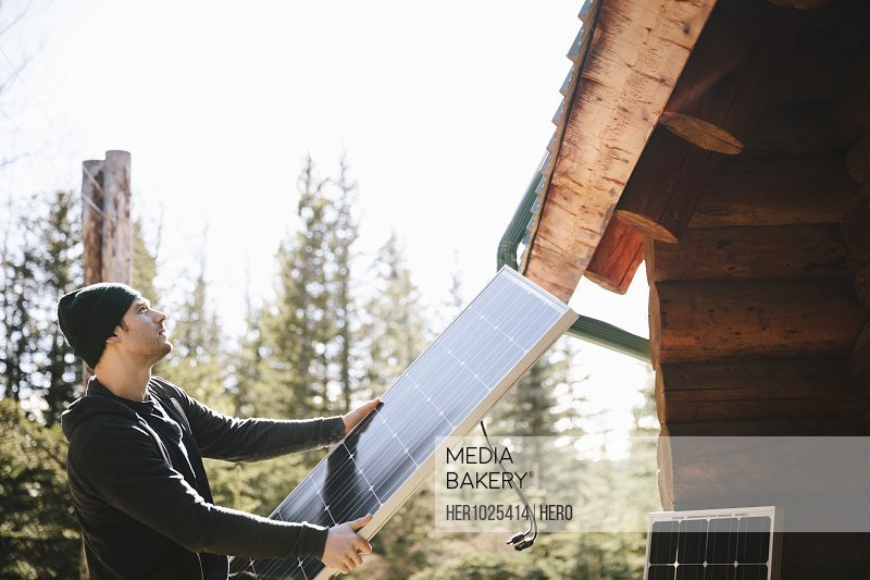 Man installing solar panels outside cabin