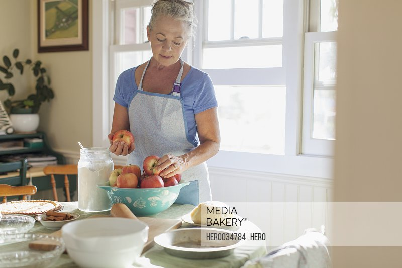 Mature woman in kitchen with apples for pie making.