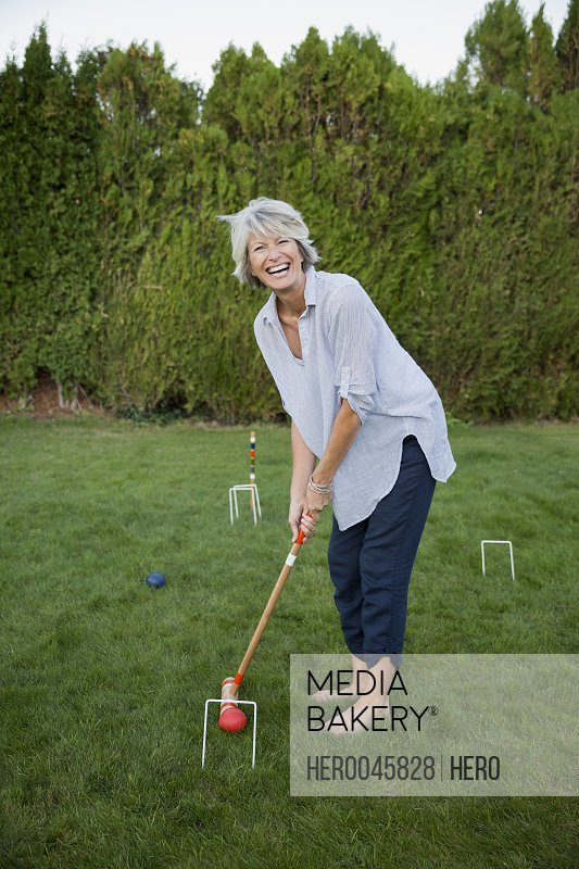 Enthusiastic woman playing croquet in summer grass