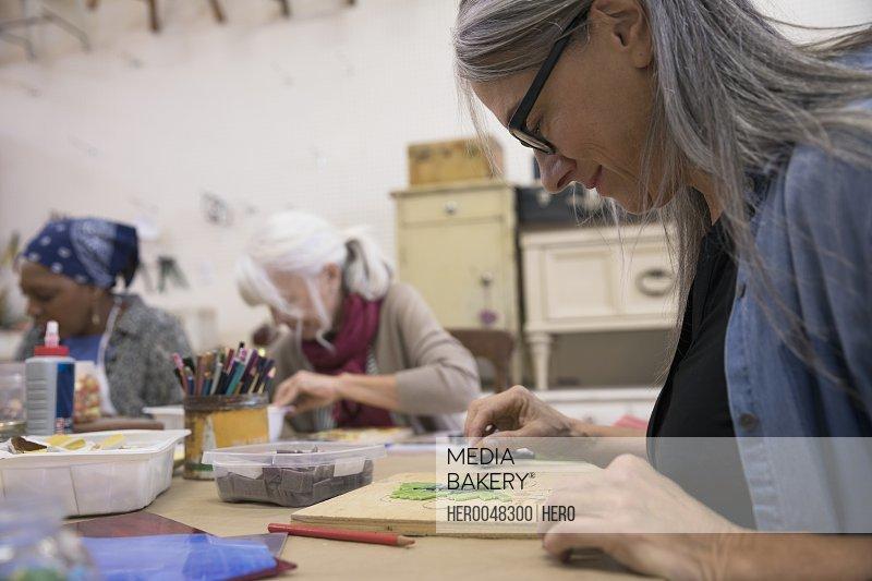 Woman enjoying mosaic art and craft class