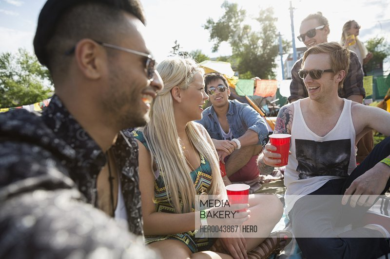 Young friends drinking and hanging out at summer music festival