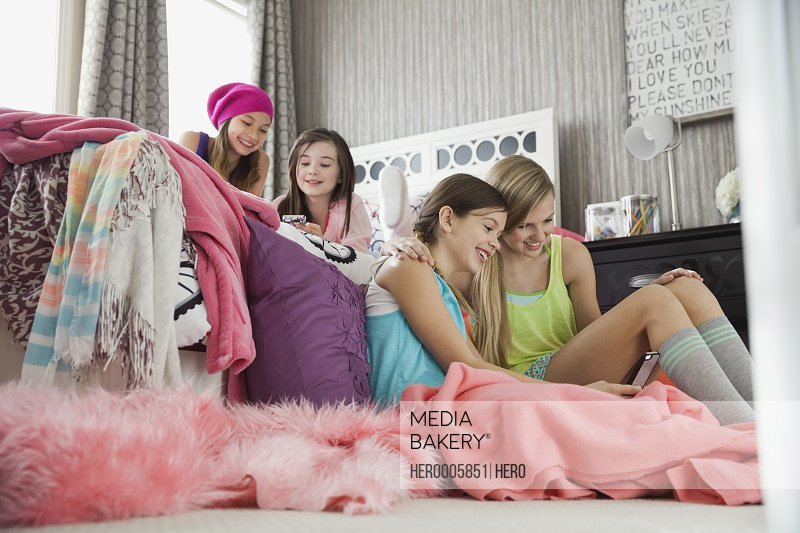 Girls using mobile phones at slumber party