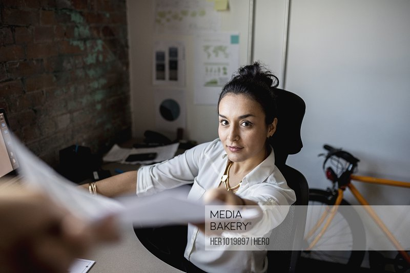 Portrait creative businesswoman reaching for paperwork in office