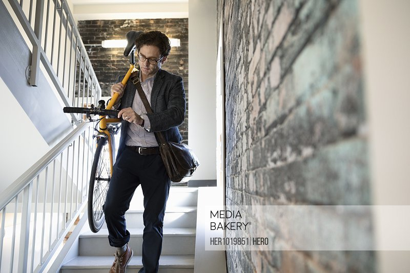 Businessman carrying bicycle down stairwell steps