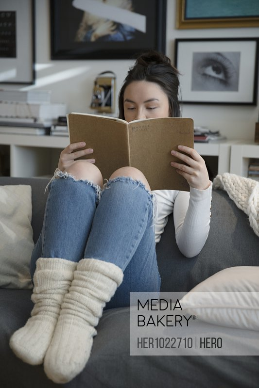 Cozy young woman reading on living room sofa