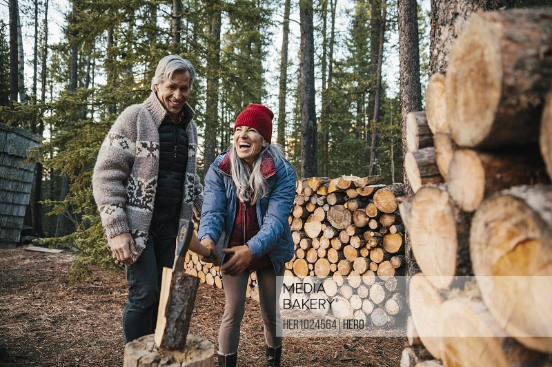 Happy couple cutting firewood