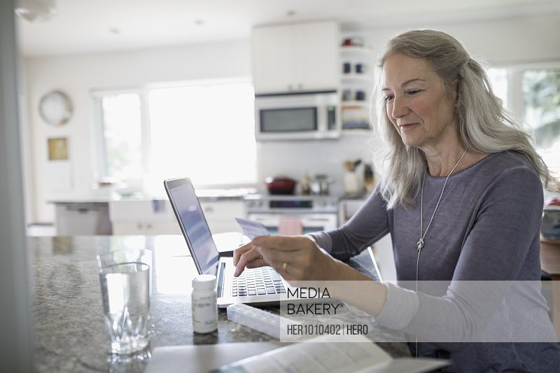 Senior woman with credit card reordering prescription medication at laptop in kitchen