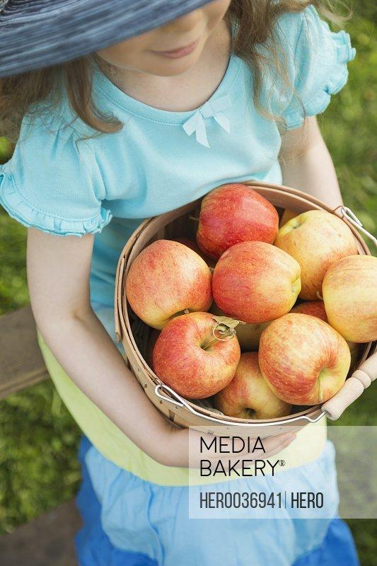 Girl holding bucket full of fresh apples
