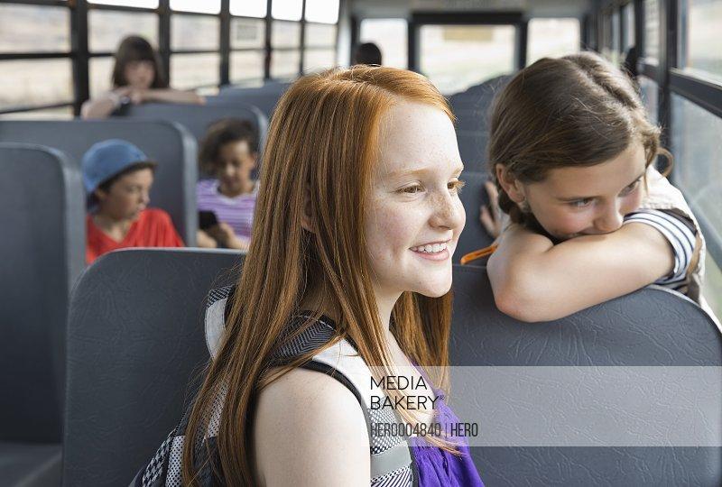 Schoolgirls looking away inside bus