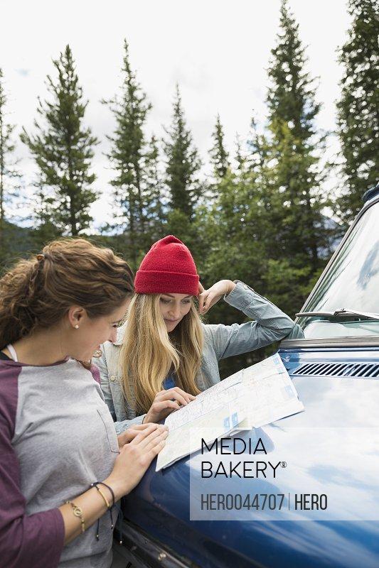 Women viewing map on camper van