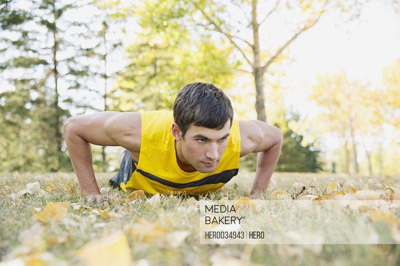 Serious young adult man doing push-ups outdoors.