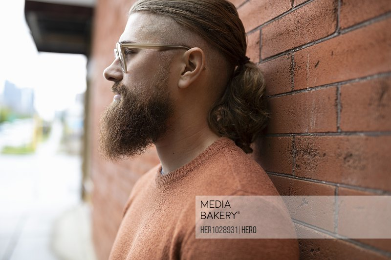 Profile portrait hipster young man with beard leaning against brick wall