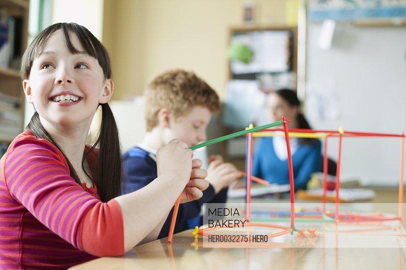elementary students using plastic building set
