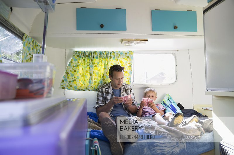 Father and son playing cards inside camper trailer