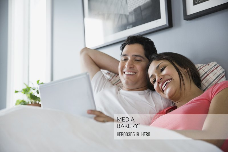 Couple in bed watching digital tablet