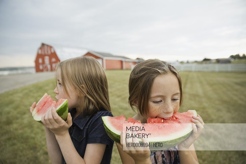 Girls eating watermelon outdoors