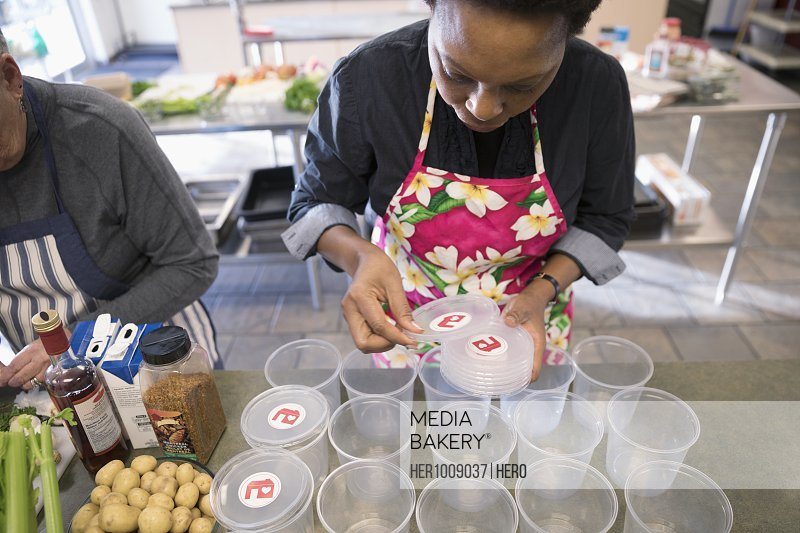 Female volunteer preparing soup containers in soup kitchen