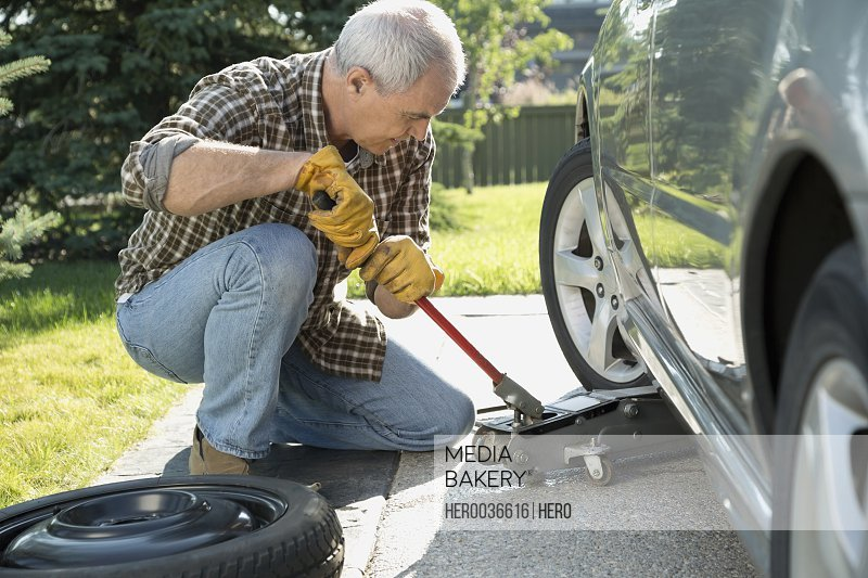 Mature man changing car tire