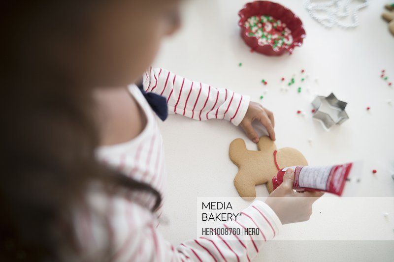 Overhead view girl decorating Christmas gingerbread cookie with red frosting