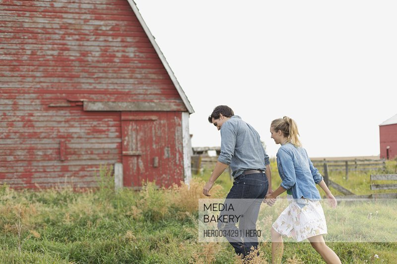 Young couple walking towards barn on rural property.