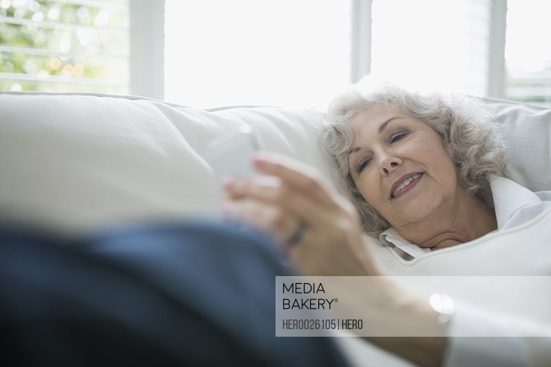 Relaxed senior woman texting on living room sofa