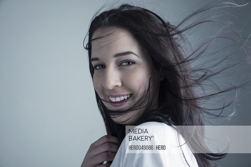 Portrait wind blowing hair of smiling brunette Caucasian young woman