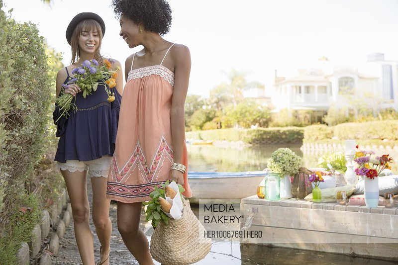 Young women with fresh flowers and picnic bag at summer lakeside