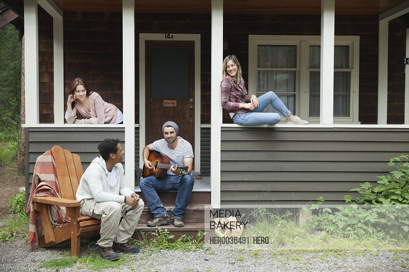 Portrait of man playing guitar for friends on cabin porch