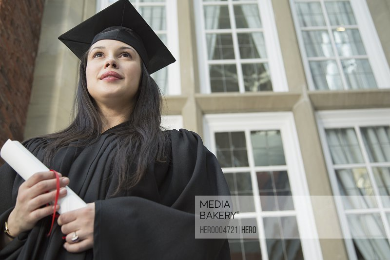 Pensive college graduate holding diploma