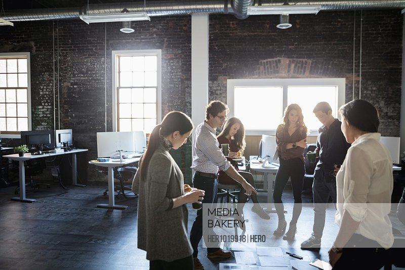 Creative business people meeting, reviewing proofs on loft office floor