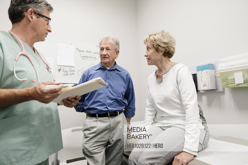Doctor with medical record talking to senior couple in clinic examination room