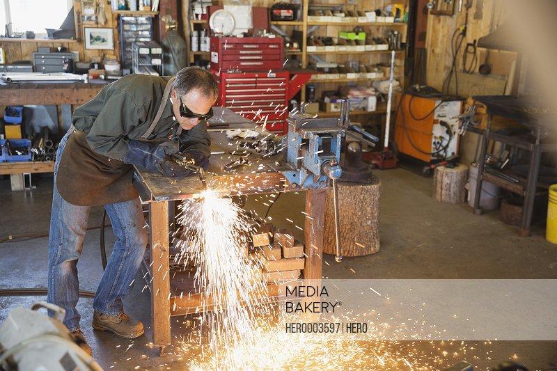 Welder using torch at workbench in workshop