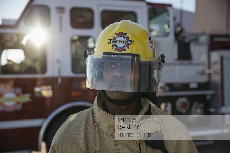 Confident, tough male firefighter wearing helmet