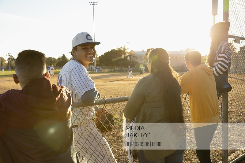 Portrait happy Latinx baseball player standing at sunny fence