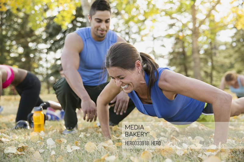 Woman determined to do push-up during outdoor fitness class.