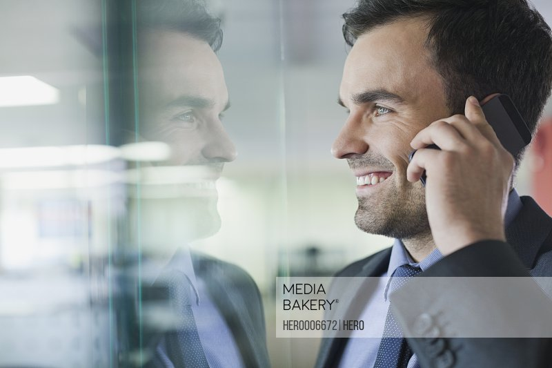 Smiling businessman using mobile phone in office